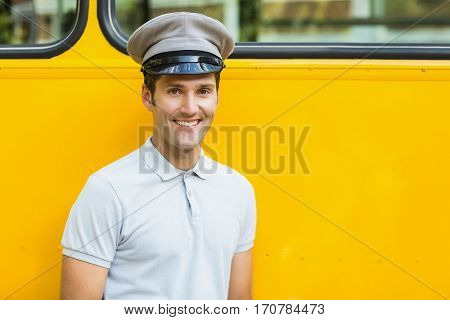 Portrait of bus driver smiling in front of bus