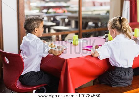 Rear view of boy and girl in school uniforms having lunch in school cafeteria