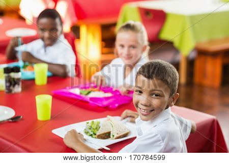 Happy children having lunch during break time in school cafeteria
