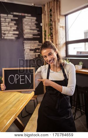 Beautiful waitress holding a sign with open in cafeteria