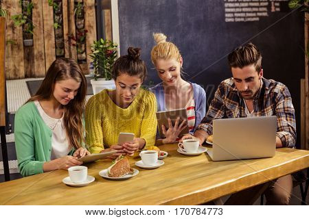 Friends using technology in a cafe