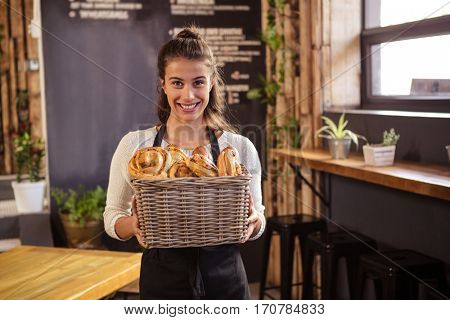 Woman holding a basket with pastries inside in a coffee shop
