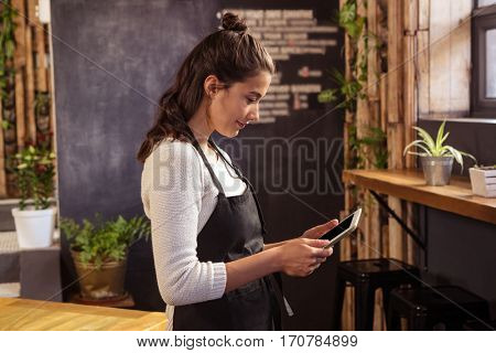 Beautiful waitress using digital tablet in cafeteria