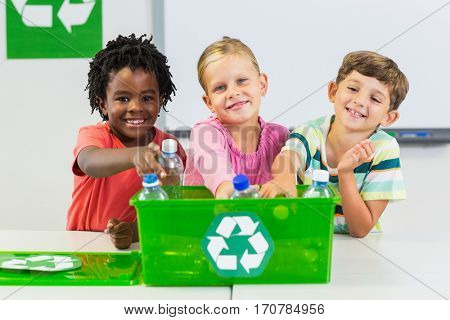 Portrait of kids holding recycled bottle in classroom