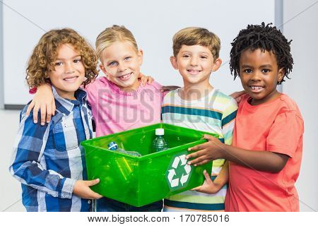 Portrait of kids holding recycled bottle in box