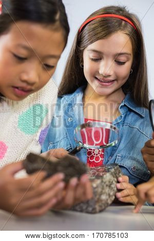 Kids looking at specimen stone through magnifying glass in classroom