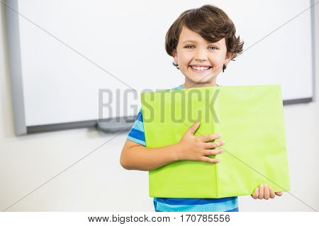 Portrait of smiling schoolboy standing with book in classroom at elementary school