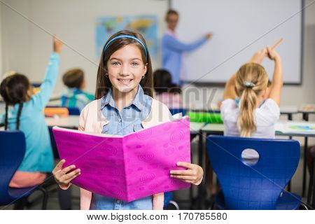Portrait of smiling schoolgirl standing with book in classroom at elementary school
