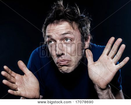 studio portrait on black background of a funny expressive caucasian man frowning ignorant