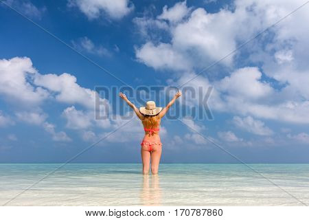 Beautiful young woman standing in the ocean with hands raised. Happy vacation in Maldives