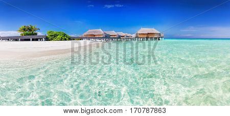 Panorama of wide sandy beach on a tropical island in Maldives. Water villas on Indian Ocean.