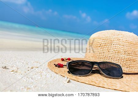Sun hat and sunglasses on sand, clear turquoise ocean in Maldives. Vacation, travel concept.