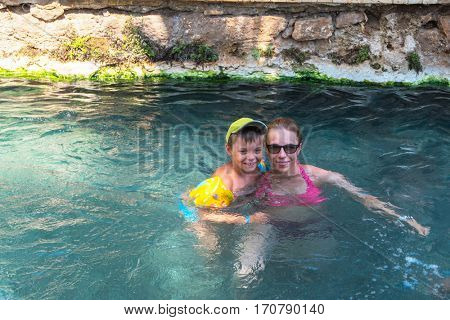 Pammukale, Turkey - July, 2015: photo of woman and her son at thermal Cleopatra pool in ancient city Hierapolis, near modern Turkey city Denizli