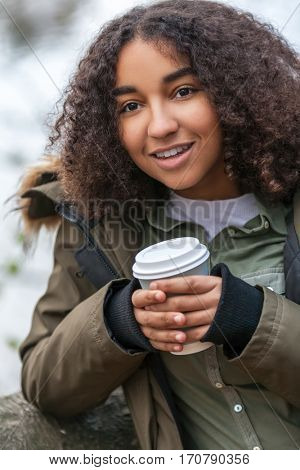 Beautiful happy mixed race African American girl teenager female young woman smiling drinking takeaway coffee outside in winter