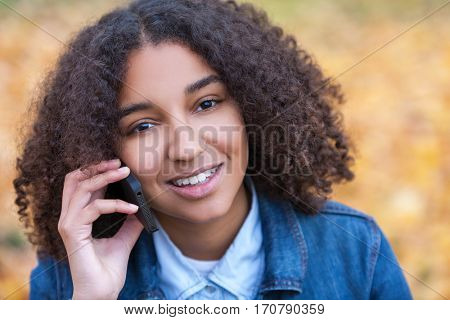 Outdoor portrait of beautiful happy mixed race African American girl teenager female young woman smiling with perfect teeth talking on cell phone