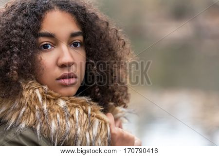 Outdoor portrait of beautiful happy mixed race African American girl teenager female child in fake fur lined coat