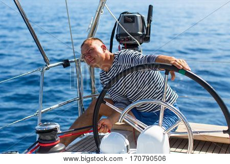 Man manages a sailing yacht during a race at sea.