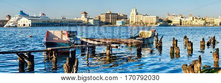 Panoramic image of the City of Havana in Cuba with a view of the Old Havana skyline and an old wooden pier with fishing boats on the bay