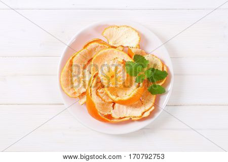 peeled orange arranged in peels on white plate