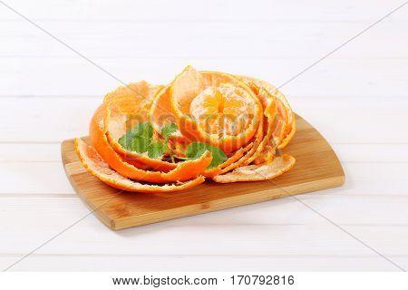 peeled orange arranged in peels on wooden cutting board