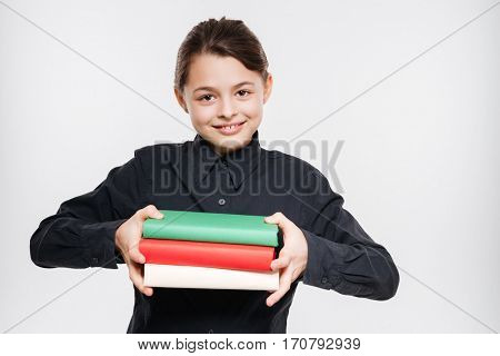Image of cheerful young girl holding books isolated over white background.