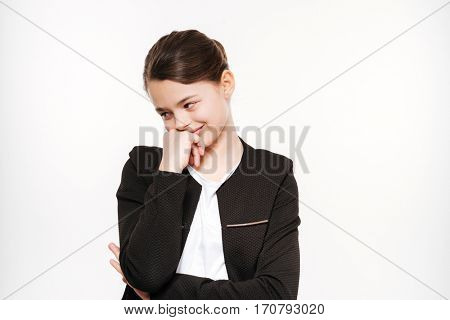 Photo of smiling young girl standing and posing isolated over white background.