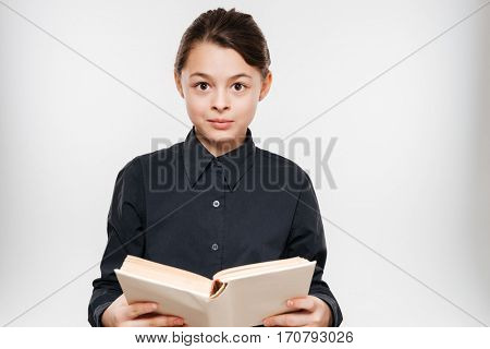 Image of cheerful young girl reading book isolated over white background.