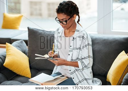 Image of young attractive african lady wearing glasses sitting in library holding book and writing notes.