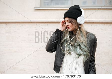 Beauty Woman in warm clothes listening music in earphone on the street and standing near the wall