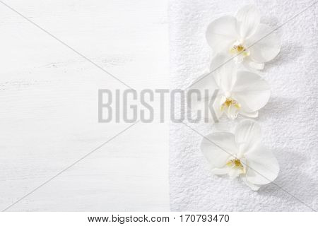 Three orchids and white terry towel  lying on shabby wooden board.  Viewed from above. Spa concept.