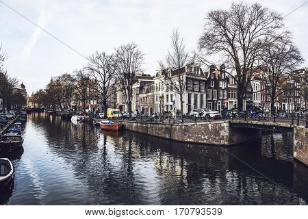 AMSTERDAM, NETHERLANDS - January 28, 2017: Water canal in Amsterdam with boats, bridge and historical canal houses surrounded by bare trees, with cloudy sky reflected in water