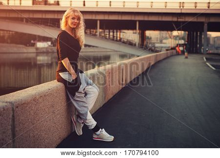 Young teenage sports style woman standing on stone quay at morning sunrise
