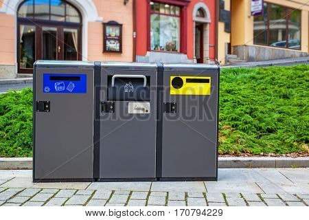 Three modern refuse bins in traditional europe city