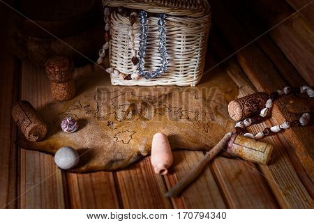 Old damaged treasure map lying on a table surrounded by assorted corks, stones, beads.