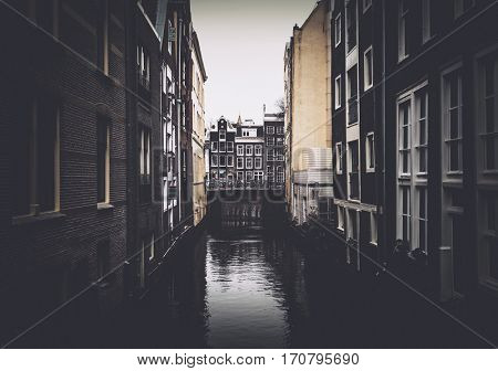 Walls of canal buildings in Amsterdam and bridge over water in distance, darkened with vignette effect