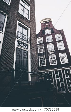 Entrance to old bricked building next to another traditional dutch canal house with neck-gable, against grey sky - Amsterdam, Netherlands