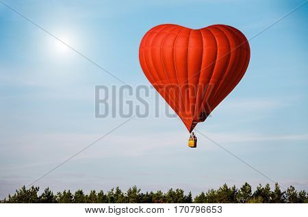 Beautiful red air balloon in the shape of heart against blue sky in a sunny bright day fly high above the trees. Romantic trip on Valentine's Day. Sports and recreation travel theme. Nature background
