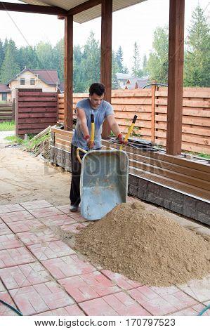 Man Unloads Sand  From A Wheelbarrow On Track