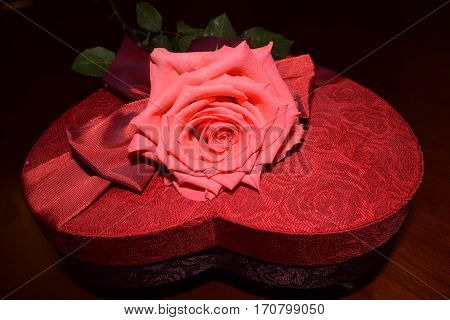Pink rose on top of heart shaped red box with red bow