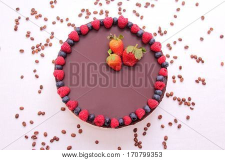 Cake souffle covered with chocolate jewelry berries raspberry blueberry blueberry strawberry white background