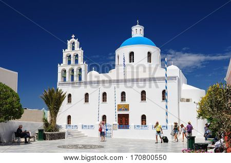 Oia, Santorini island, Cyclades, Greece - April 23, 2016: People relaxing near the Orthodox church of Panagia with bell tower at central square. Oia is a small town and former community in the South