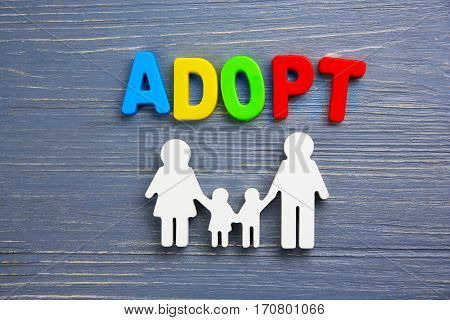 Word ADOPT and figure in shape of family on color wooden background