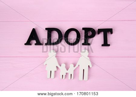 Word ADOPT and figure in shape of happy family on wooden background