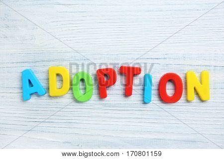 Word ADOPTION on light wooden background