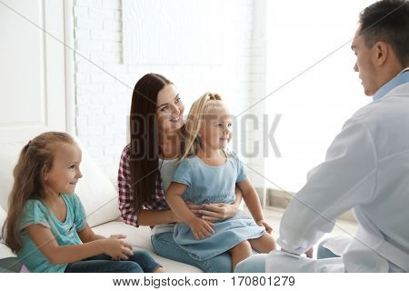 Mother with daughters visiting pediatrician doctor at clinic