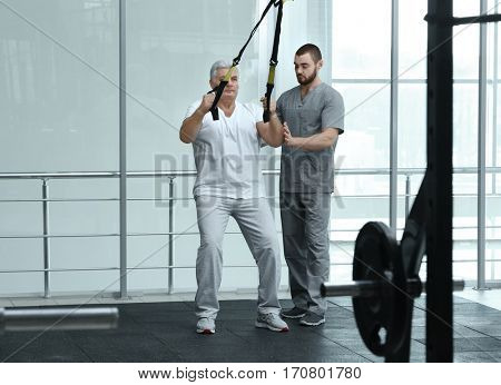 Rehabilitation concept. Mature man doing exercises under physiotherapist supervision