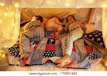 Cute little children sleeping in hovel at home