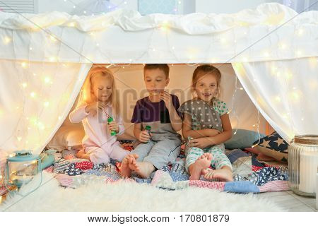 Cute little children blowing soap bubbles in hovel at home