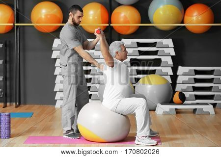 Rehabilitation concept. Mature man doing exercises under physiotherapist supervision