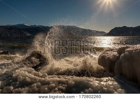 A colorful view of the sea the mountains the sun and the ice on the rocks through the scenic spray from the movement of waves in the winter